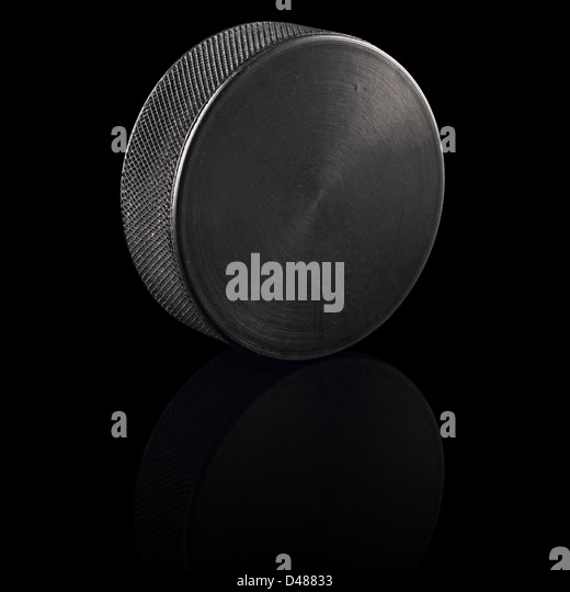ice hockey puck in front of black background - Stock Image