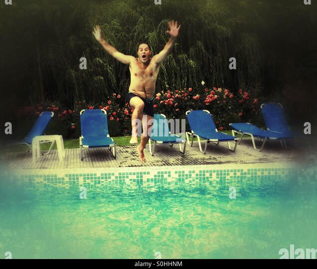 Man jump into a pool - Stock Image
