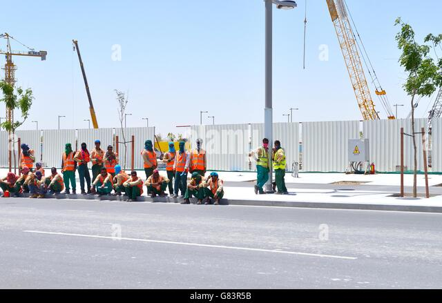 Marina District of rapidly developing new city of Lusail, Qatar. Immigrant building site construction workers wait - Stock Image