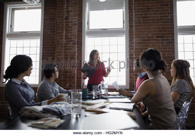 Female designer leading meeting in conference room - Stock Image