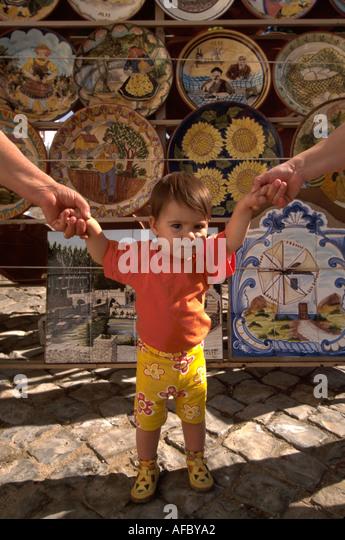 Portugal Algarve Alte child toddler parent's hands ceramic plates souvenirs - Stock Image
