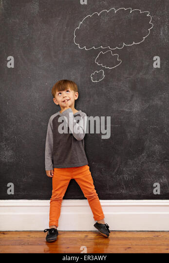 Child thinking with a thought bubble on the blackboard. Full length shot of cute little boy standing at home. Inspiration - Stock Image