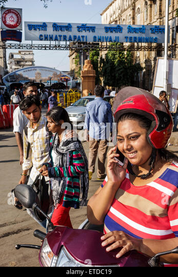 India Indian Asian Mumbai Fort Mumbai Chhatrapati Shivaji Railway Station Terminus Area woman motor scooter smartphone - Stock Image