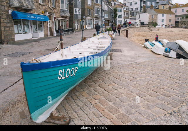 The St Ives Pilot Gig Sloop on the quayside in Cornwall. - Stock Image
