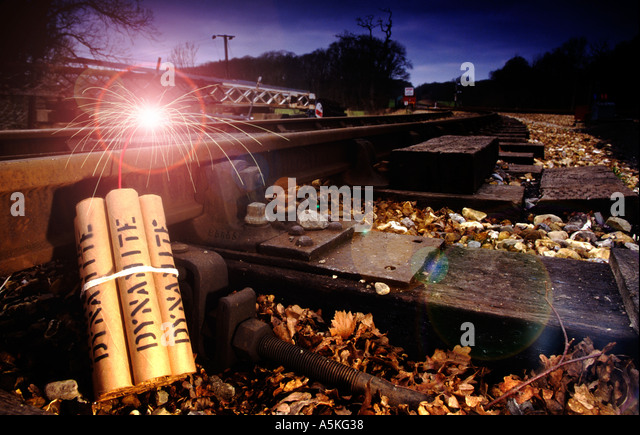 dynamite with fuse burning against railway track - Stock Image
