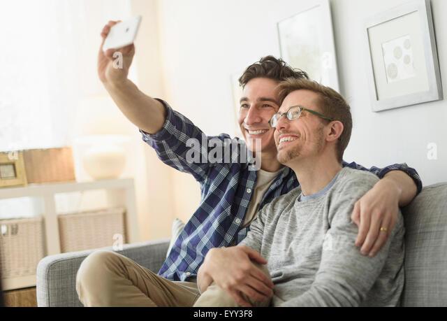 Caucasian gay couple taking selfie on sofa - Stock Image