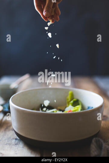 Ingredients for Wasabi Caesar Salad (gluten-free). Sprinkling parmesan cheese. - Stock Image