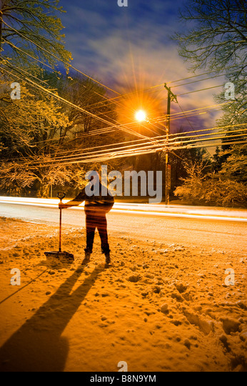 Man Shoveling Snow At Sunrise With Street Light Behind Him, USA - Stock-Bilder