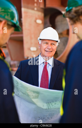 Workers reading blueprints on dry dock - Stock Image