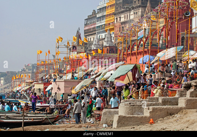 Hindu pilgrims gathering at a ghat to bathe in the Ganges river in Varanasi, Uttar Pradesh, India - Stock Image
