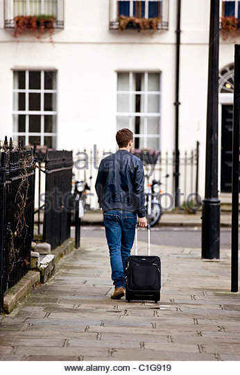 A young man pulling his suitcase in the street, back view - Stock-Bilder