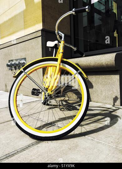 Yellow bike in the city - Stock Image