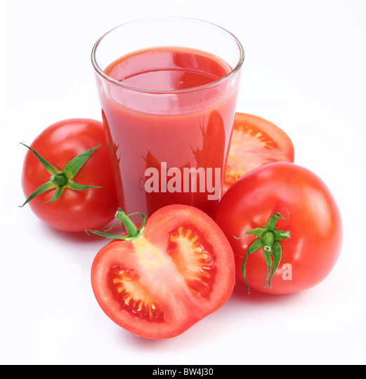 Full glass of fresh tomato juice and vegetables near it. - Stock Image