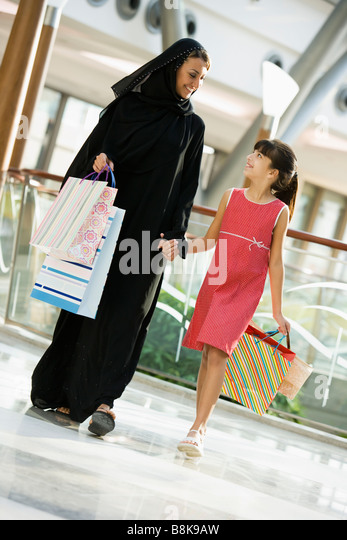 Woman and young girl walking in mall smiling (selective focus) - Stock Image