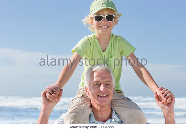 Portrait of smiling grandfather carrying grandson on shoulders on sunny beach - Stock Image