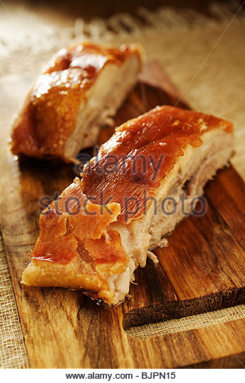Roast belly pork on chopping board - Stock Image