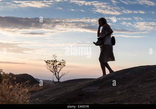 silhouette of woman on phone walking barefoot through remote hills at dusk holding shoes in hands - Stock Image