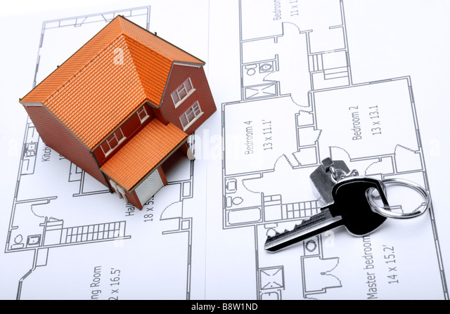 A model home and house key on architectural floor plans for an extension - Stock Image