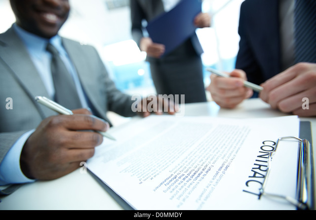 Image of contract on workplace and group of partners making decision to sign it - Stock Image