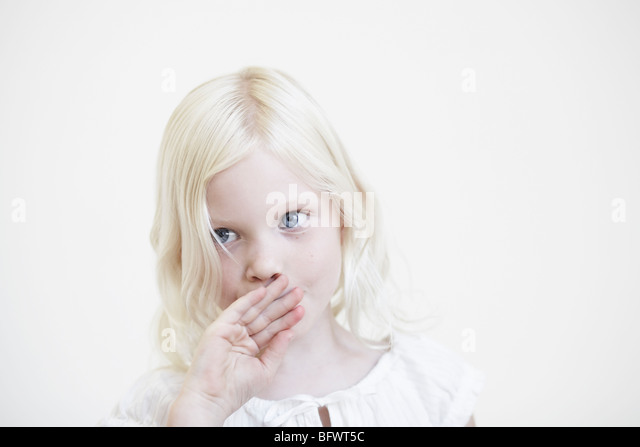 Young girl with hand up to mouth - Stock Image