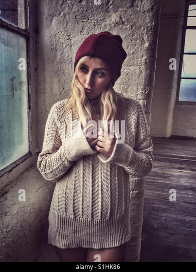 Beautiful young blond woman wearing a Will hat and jumper standing by the window looking away - Stock-Bilder