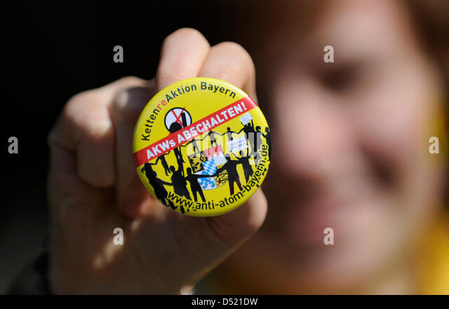A young woman presents a button with the phrase 'Shut down nuclear power plants' during a demonstration - Stock Image