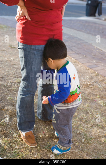 shy two year old boy hides, facing mother, outdoors - Stock Image