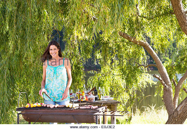 Woman Cooking Barbeque In Countryside - Stock Image