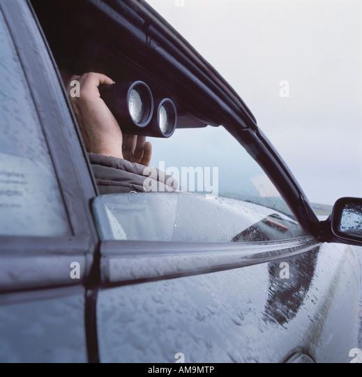 Man with binoculars peeking through car window. - Stock-Bilder