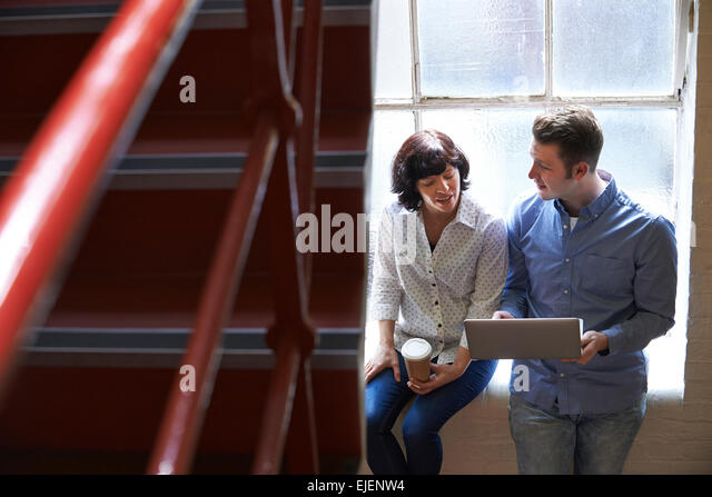 Two Businesspeople Having Informal Meeting On Office Stairs - Stock Image