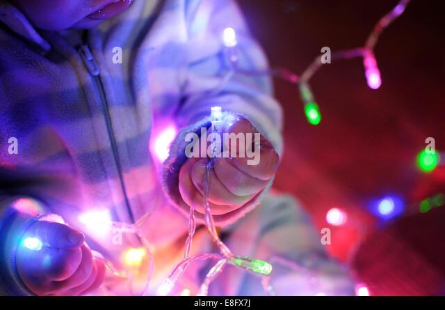 USA, Indiana, Baby boy grabs holiday lights - Stock-Bilder