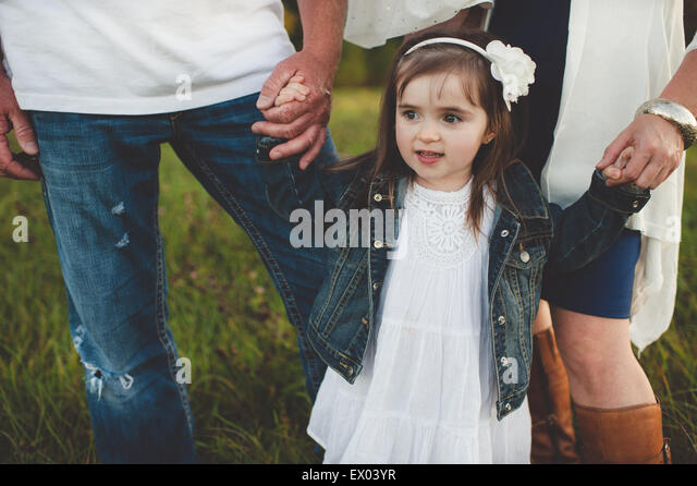 Young girl holding her parent's hands, low section - Stock Image
