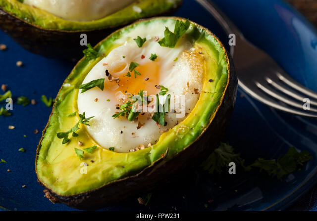 Homemade Organic Egg Baked in Avocado with Salt and Pepper - Stock Image