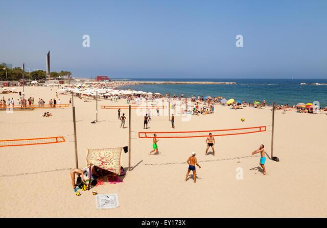 People playing volleyball on Platja Nova Icaria beach, Port Olimpic, Barcelona, Spain Europe - Stock Image