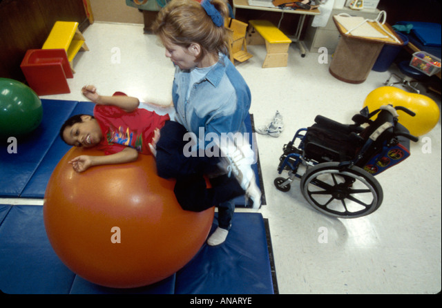 New Jersey East Orange Cerebral Palsy Center disabled student female therapist Hispanic boy ball - Stock Image