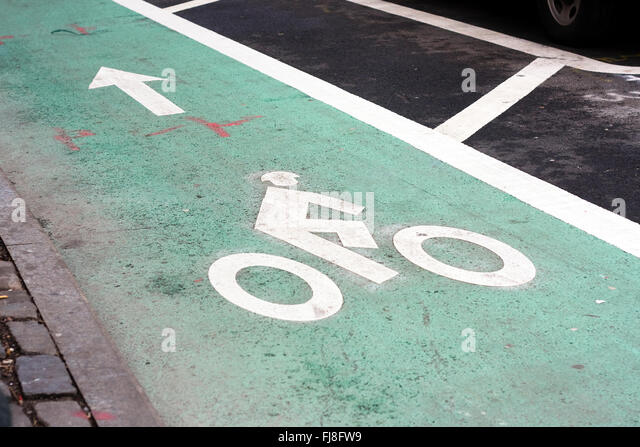 Green paint on road designating a dedicated bike lane with a bike rider symbol and arrow painted in white on ground - Stock-Bilder