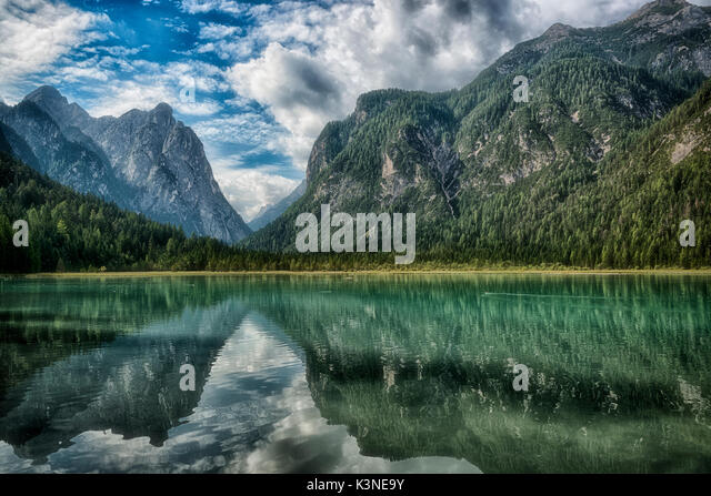 Lake of Toblach surrounded by mountains with blue sky and clouds in the background on a summer day, Sud Tirol, Italy - Stock Image