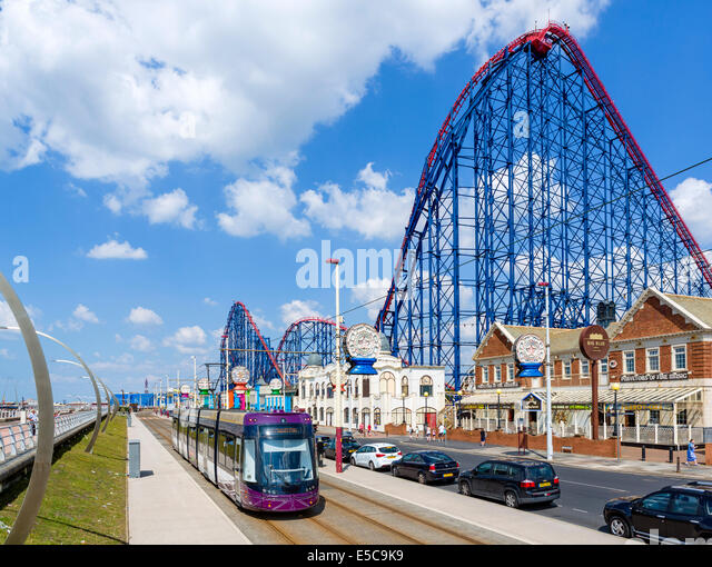 Tram on the promenade in front of the Big One roller-coaster at the Pleasure Beach amusement park, Blackpool, Lancashire, - Stock Image