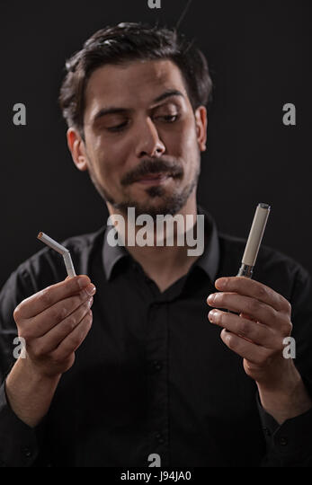 Portrait of man who is decided to quit smoking cigarette in favor of electronic cigarette. - Stock Image