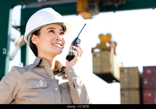 shipping industry worker directing cranes with her walkie-talkie - Stock Image