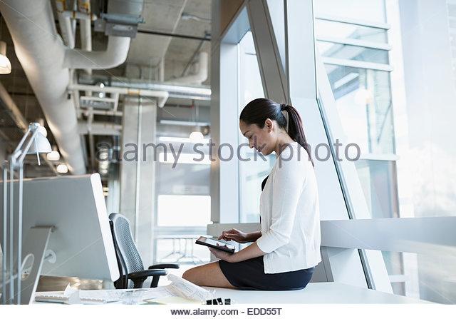 Businesswoman using digital tablet on office desk - Stock Image