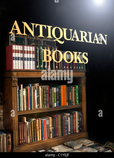Antiquarian Bookshop window with sign and antique books and bookcase on display - Stock-Bilder