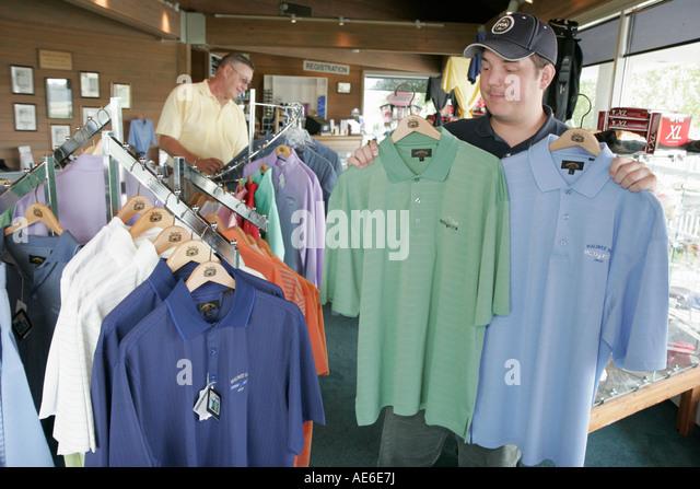 Toledo Ohio Oregon Maumee Bay State Park Scottish Links Golf Course pro shop shirts man shopping - Stock Image
