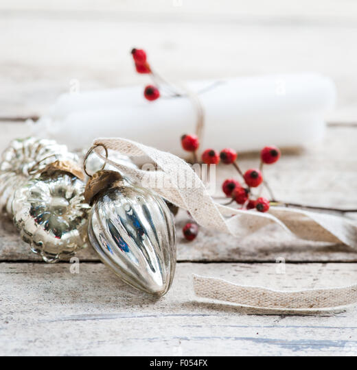 white candles tied with twine, red berries and silver baubles - Stock Image