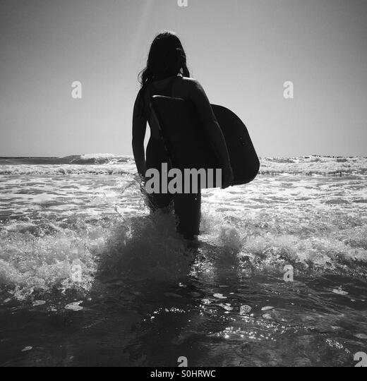 Girl about to go boogie boarding, Falasarna beach, Crete, Greece - Stock Image