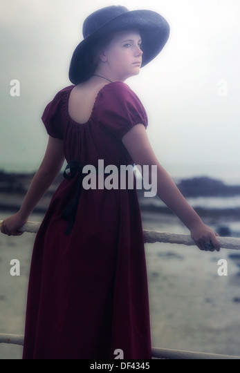 a young girl in a red dress is standing at a white bannister at the sea - Stock Image