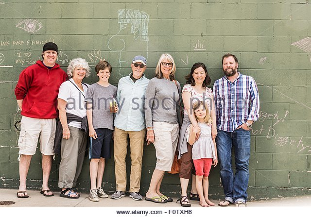 Three generation family in front of wall, portrait - Stock-Bilder