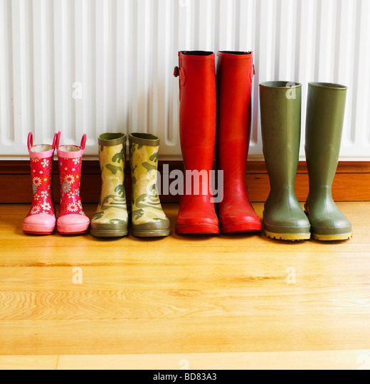 A family's Wellington Boots line up  drying in front of a radiator. - Stock-Bilder