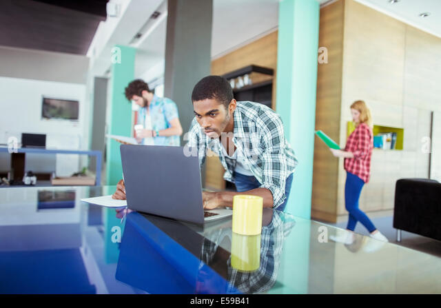 Man working on laptop in office - Stock-Bilder