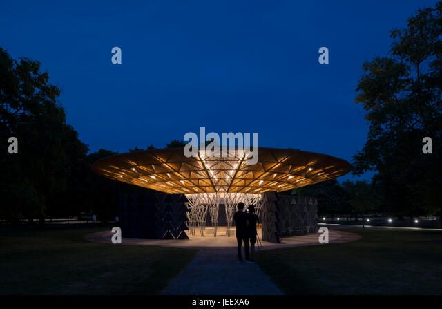 Night time view with people in silhouette. Serpentine Summer Pavilion 2017, London, United Kingdom. Architect: Diebedo - Stock-Bilder